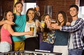 Portrait of happy friends toasting with mixed drink and beer in a bar