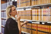 Lawyer wearing glasses and looking for a book in the shelf in library