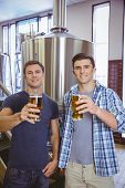 Young men holding a pint of beer smiling at camera in the factory