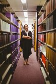 Stern lawyer standing between shelfs with arms crossed in library