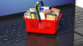 Shopping hand basket full with products on laptops keyboard