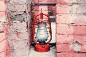 Kerosene lamp on ruined brick wall background