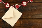 Love letter hanging on rope on rustic wooden background