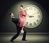 tired businessman carrying his smiling wife against a background of a big clock.