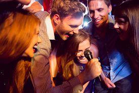 stock photo of karaoke  - Happy friends singing karaoke together at the nightclub - JPG