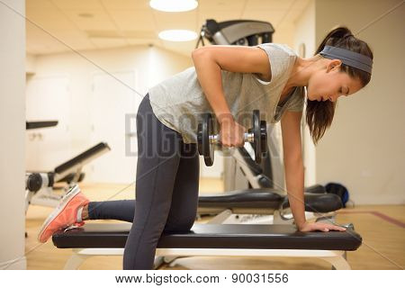 poster of Fitness gym woman strength training lifting dumbbell weights in Bent-over One-Arm Dumbbell Row. Fema