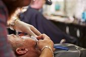 stock photo of barber razor  - Barber Shaving Client With Cut Throat Razor - JPG