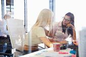 stock photo of coworkers  - Women coworkers talking in an office - JPG