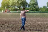 foto of hoe  - Rear view of attractive farmer carrying hoe on shoulders in corn field in spring tractor in background - JPG