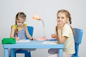 foto of 6 year old  - Two girls of four and six years of sitting at the table and draws and paints and pencils - JPG