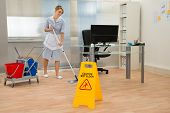 stock photo of maids  - Young Maid Cleaning Floor With Mop In Office - JPG