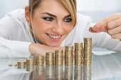 stock photo of golden coin  - Young Happy Businesswoman Putting Coin On Stack Of Golden Coins  - JPG