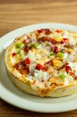 stock photo of deep  - A personal sized deep dish pizza on a white plate sitting on a wooden table - JPG