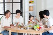 stock photo of multi-generation  - Asian family eating at home - JPG