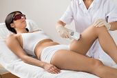 foto of thighs  - Beautician Giving Epilation Laser Treatment To Woman On Thigh - JPG