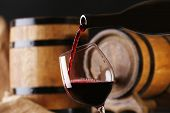 image of merlot  - Pouring red wine from bottle into glass with wooden wine casks on background - JPG