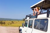 image of observed  - Young blond lady on safari standing in open roof jeep observing wild animals through binoculars.