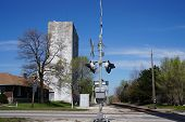 image of elevators  - A railroad crossing gate with an old grain elevator in the background - JPG