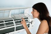 image of check  - Young Woman Checking Air Conditioner In House - JPG