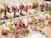 foto of spit-roast  - birds on the spit with meat bacon and sage ready for roasting - JPG
