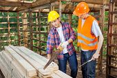image of timber  - Construction workers working together in timber cabin at site - JPG