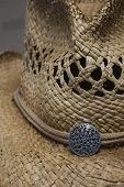 image of cowgirls  - A close up photo of a straw cowgirl hat with a silver ornament hatband - JPG