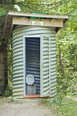 image of outhouses  - An outhouse made with a thick pipe sitting in the forest - JPG