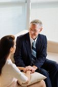 stock photo of psychologist  - Smiling mature male psychologist reassuring his patient - JPG