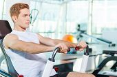 foto of concentration man  - Handsome young man looking concentrated while working out in gym - JPG