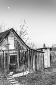 image of outhouses  - Moon shining over a wooden rustic village shed with outhouse and moon in a cloudless sky - JPG