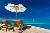 stock photo of infinity  - Deck chairs with umbrella overlooking infinity pool and tropical lagoon - JPG