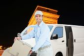 picture of charles de gaulle  - Confident delivery man pushing trolley of cardboard boxes against arc de triumphe in france - JPG