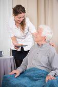 image of older men  - Young caring nurse giving the dessert to older nice man - JPG