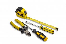 foto of measurement  - Yellow tape measure to measure the dimensions of the metric system nippers and two flat screwdriver with a yellow handle on light background - JPG