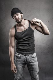 pic of frown  - Perplexed rough casual man standing holding a wrench resting on his shoulder staring at the camera with a puzzled frown over a textured grey background - JPG