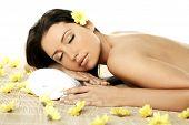 picture of beautiful brunette woman  - portrait of fresh and beautiful brunette woman laying on bamboo mat around yellow flowers - JPG