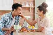 Love And Care Concept. Lovely Couple Have Fun Together: Caring Woman Feeds Husband With Croissant, B poster
