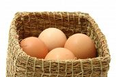 Four Brown Eggs In Wooden Straw Box Isolated On White, Soft Focus. poster