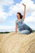 Woman having fun sitting on hay bale