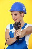 Pretty young woman using drill like a gun