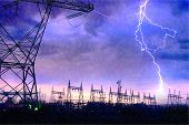 stock photo of electricity pylon  - Dramatic Image of Power Distribution Station with Lightning Striking Electricity Towers - JPG