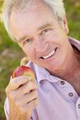 Senior man eating apple
