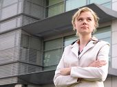 Businesswoman Standing Outside A Modern Office Building poster