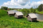 Russian Wooden Houses At A River Bank. Huts On