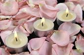 Tres velas ardientes rodeados de pétalos de rosa