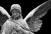 stock photo of cherubim  - Old angel statue on a graveyard isolated on black - JPG