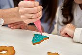 Christmas Treats. Handmade cookies, confection standing on the table. Female hands decorating ginger poster