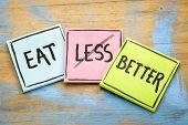 eat better (not less) - healthy eating concept - handwriting on sticky notes against grunge wood poster