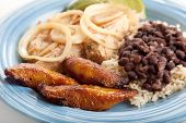 Closeup of Cuban dinner with focus on fried sweet plantains.  Marinated roast pork with black beans