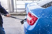 Using A Brush To Wash A Car On A Car Washing Facility On Sunny Summer Day.manual Car Wash With Press poster
